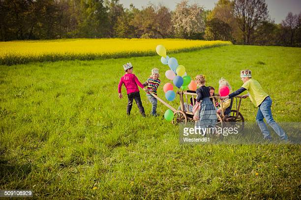 Six children on the move with wooden trolley and balloons