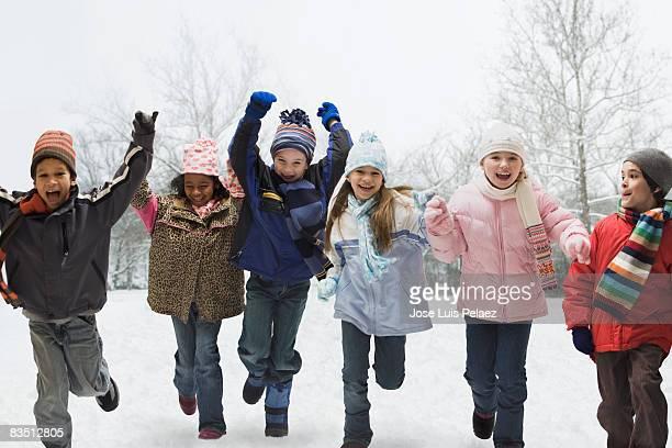 Six children running in the snow