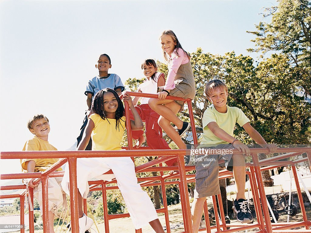 Six Children Sitting On a Climbing Frame Looking at the Camera