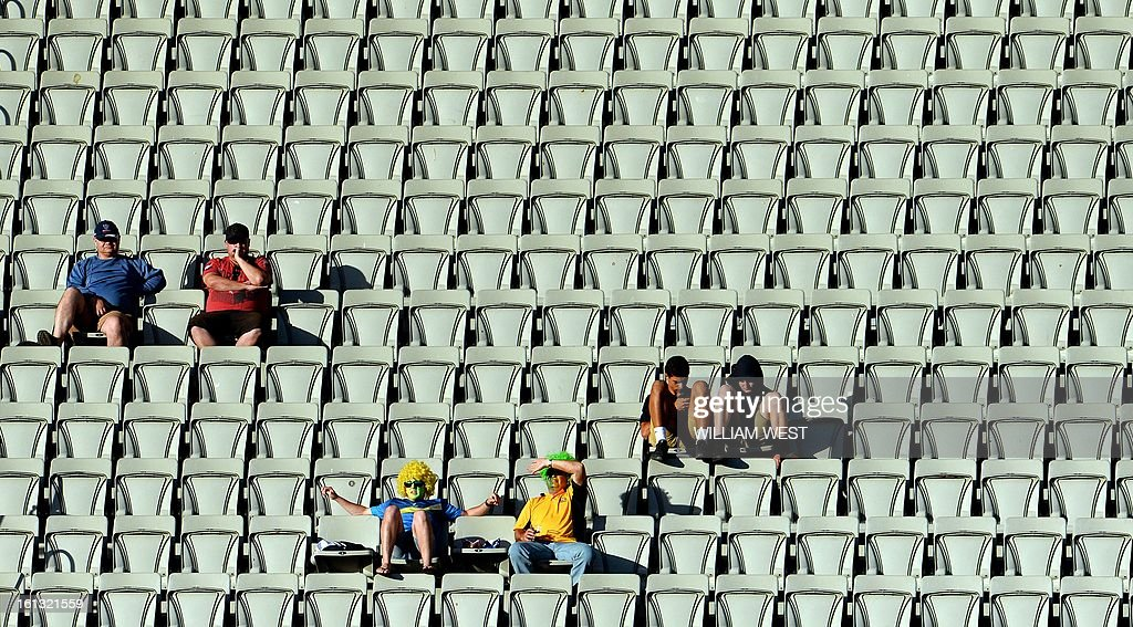 Six cricket fans watch Australia play the West Indies in their one-day cricket international played at the Melbourne Cricket Ground (MCG), on February 10, 2013. AFP PHOTO/William WEST IMAGE