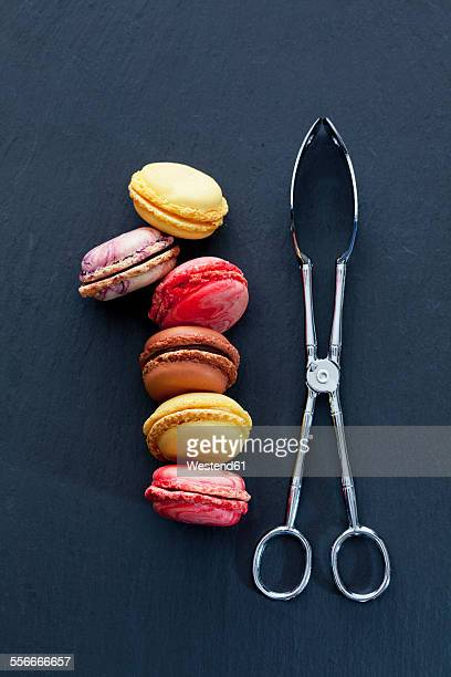 Six different macarons and a pastry tong on slate