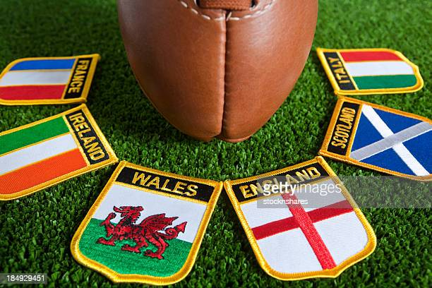 Six different nation's badges for rugby around a rugby ball