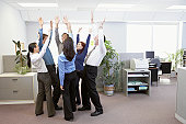 Six executives cheering in office, arms raised