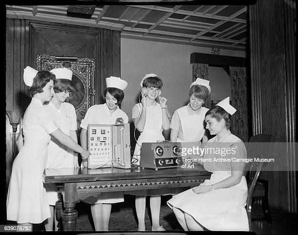 Six female nurses gathered around table with vision and hearing test machines in room with painting of mother and child circa 19501965