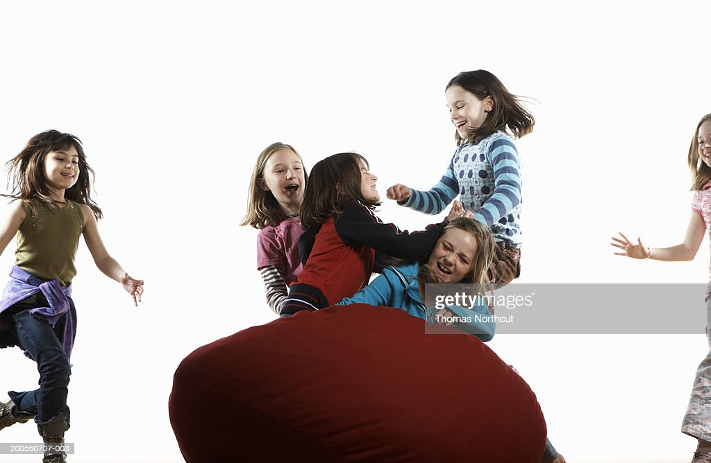 Six girls (8-10) roughhousing on bean bag, laughing : Stock Photo