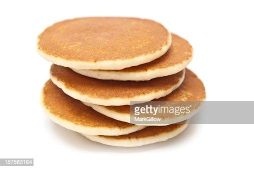 Six golden brown pancakes stacked in uneven arrangement