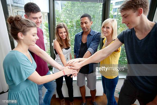 Six Happy College Students with Hands on Stack, Indoors