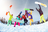 Ski concept with group of six friends. Happy snowboarders are having fun
