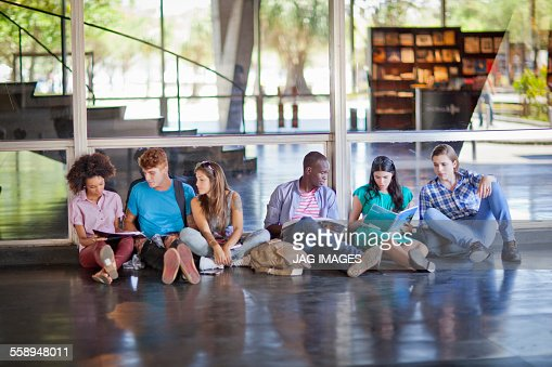 Six higher education students sitting on floor : Stock Photo