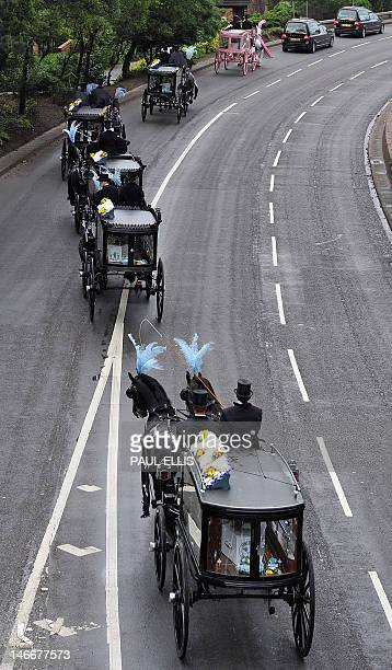 Six horse drawn carriages bearing the bodies of six children who died in a house fire are driven to St Mary's Church in Derby central England for a...