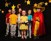 Group of six boys and girls in stargazers costumes watching handmade stars and moon against black background