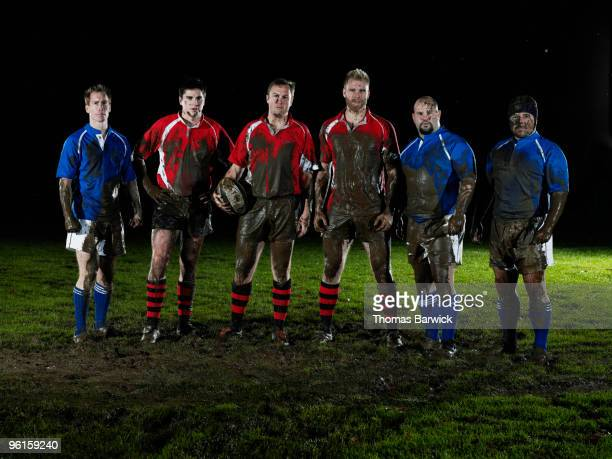 Six male rugby players covered in mud on field
