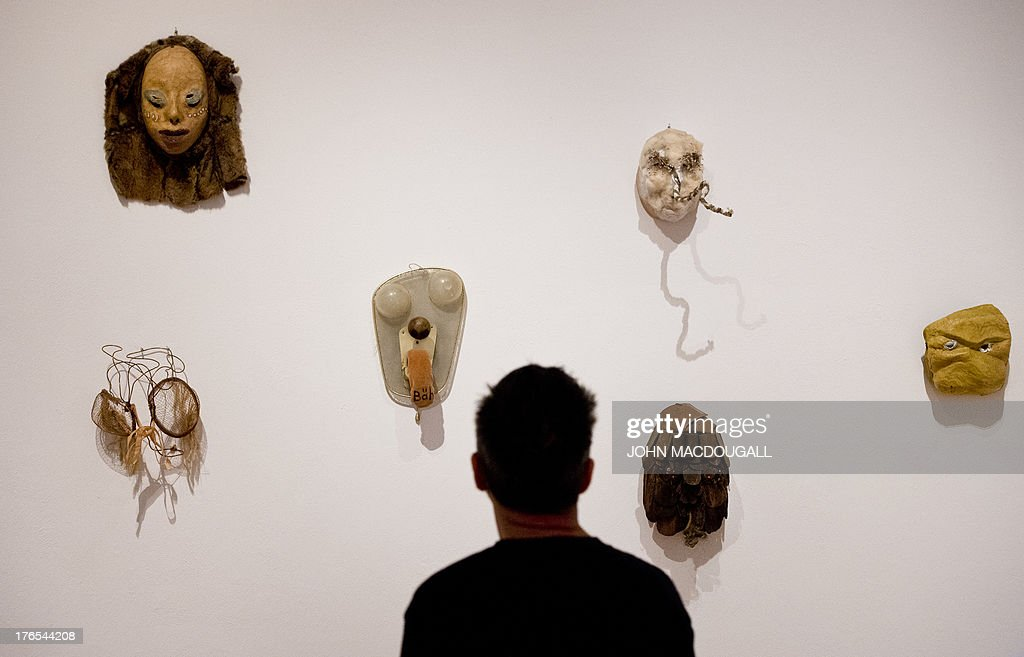 Six masks by German-born Swiss artist Meret Oppenheim (from L to R, top to bottom) 'Scar-jewelry Mask', 'Wire-eyes', 'Mask with Baaa Tongue', 'White Cotton - 1976', 'Cadavre Exquis Mask - 1971' and 'Yellow Mask - 1936' are on display at the Meret Oppenheim Retrospective in Berlin on August 15, 2013. The retrospective at the Martin-Gropius-Bau marks the centenary of the surrealist artist's birth in Berlin on 6 October 1913, and opens from 16 August to 1 December 2013. AFP PHOTO / JOHN MACDOUGALL