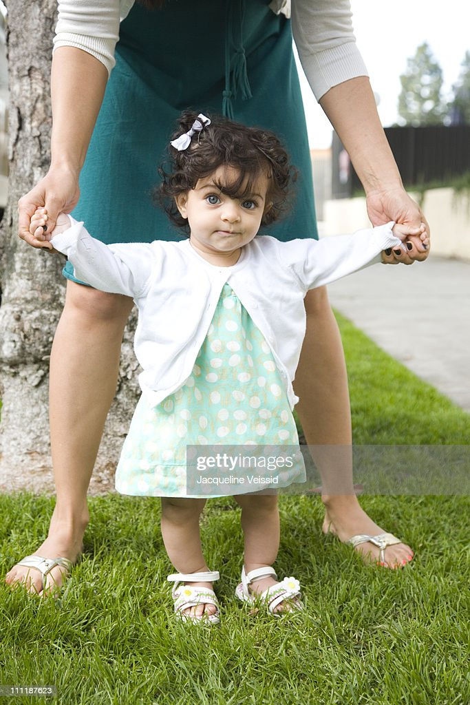 Six month old girl standing : Stock Photo