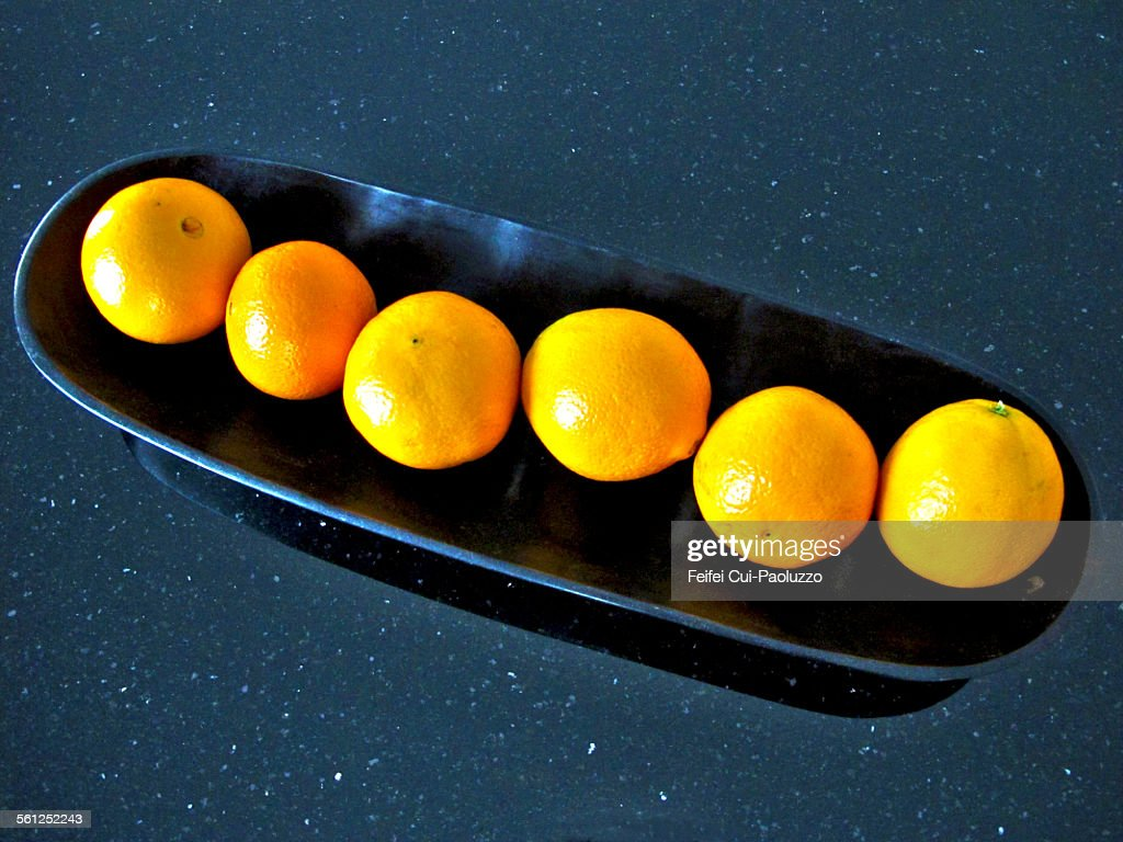 Six oranges in a black plate