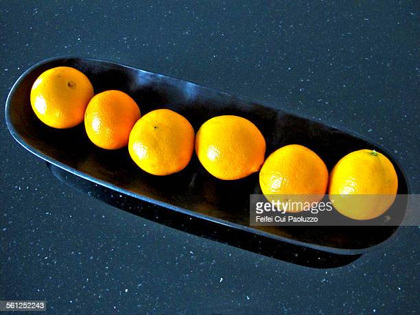 Six oranges in a black plate