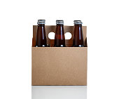 Six glass bottles of beer in brown cardboard carrier isolated on white with reflection