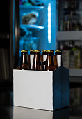 Six pack of brown beer bottles in plain white cardboard carrier with copy space on stainless steel kitchen or bar counter. Open fridge or refrigerator out of focus in rear.