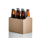 Angled view of a six pack of glass bottled beer in generic brown cardboard carrier isolated on white with reflection