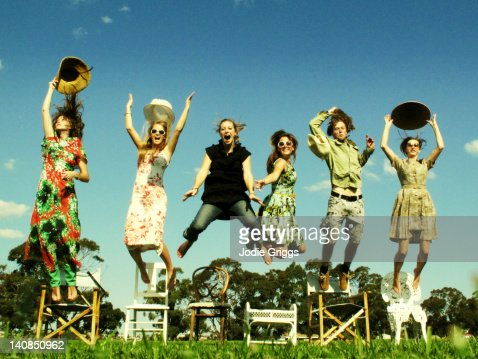 Six people jumping off chairs and throwing hats : Stock Photo