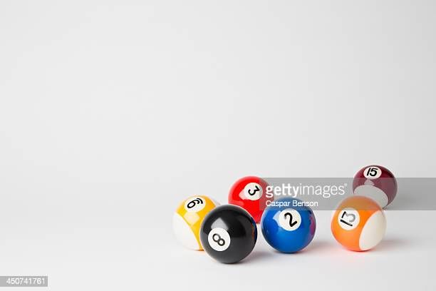 Six pool balls, including the eight ball, on a white surface