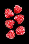 Six raspberries on black background