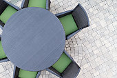 Six seater outdoor patio set with comfortable green cushions and a round dining table on a brick paved open-air patio with copyspace, overhead view
