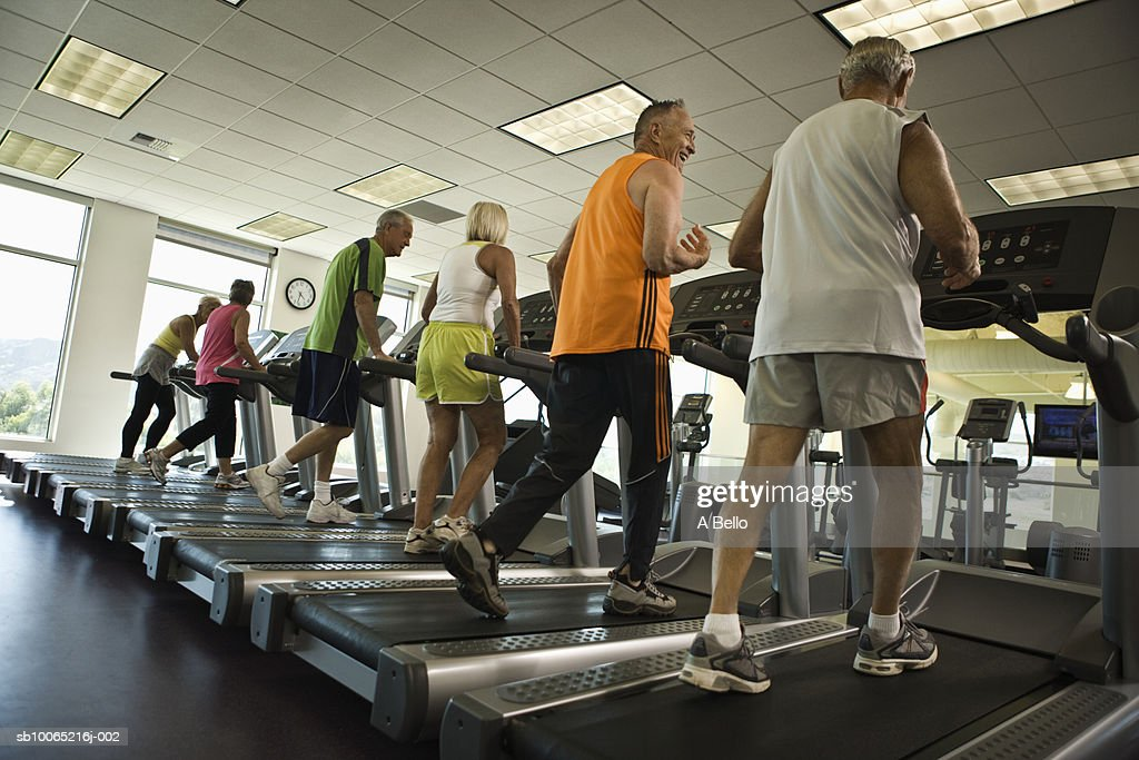 Six senior people exercising on treadmills, rear view : Stock Photo