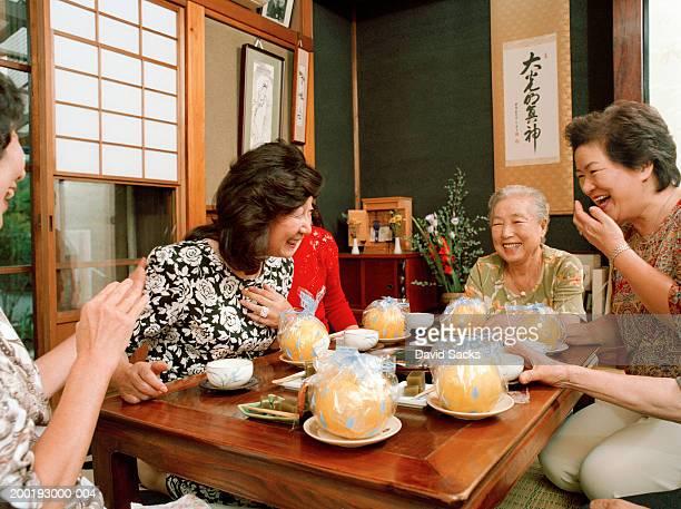 Six senior women having tea, laughing
