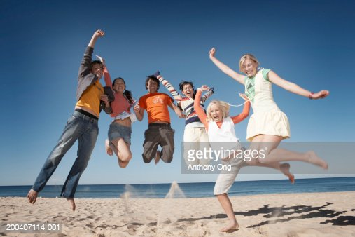 Six teenage boys and girls (16-18) jumping on beach, smiling, portrait : Stock Photo