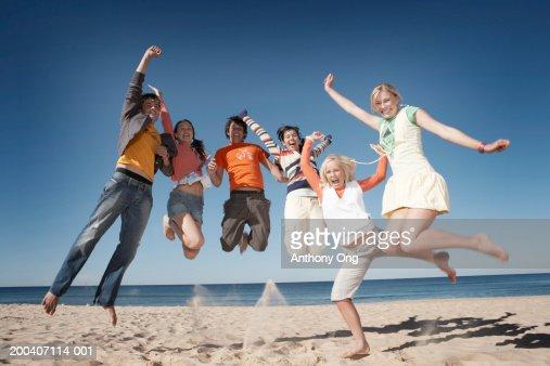 Six teenage boys and girls (16-18) jumping on beach, smiling, portrait : Foto de stock