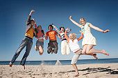 Six teenage boys and girls (16-18) jumping on beach, smiling, portrait