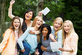 Six Teenage Girls Celebrating Successful Exam Results Smiling To Camera