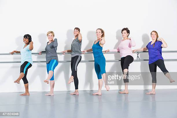 Six women doing barre exercises standing in a row