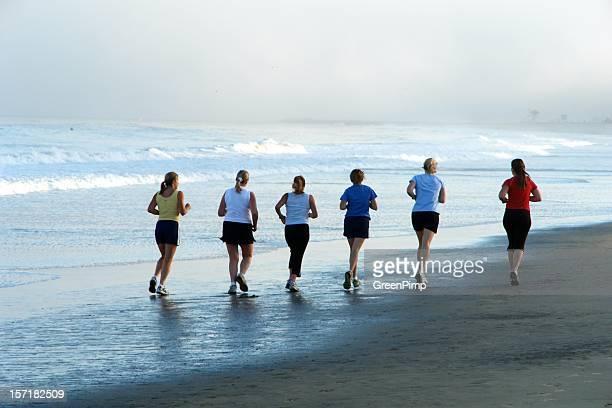 Seis mujeres ejercicio por la mañana de la playa