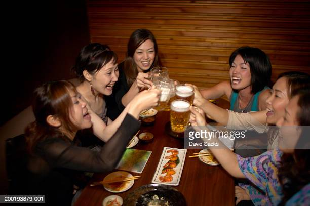 Six women toasting beer mugs in restaurant, side view