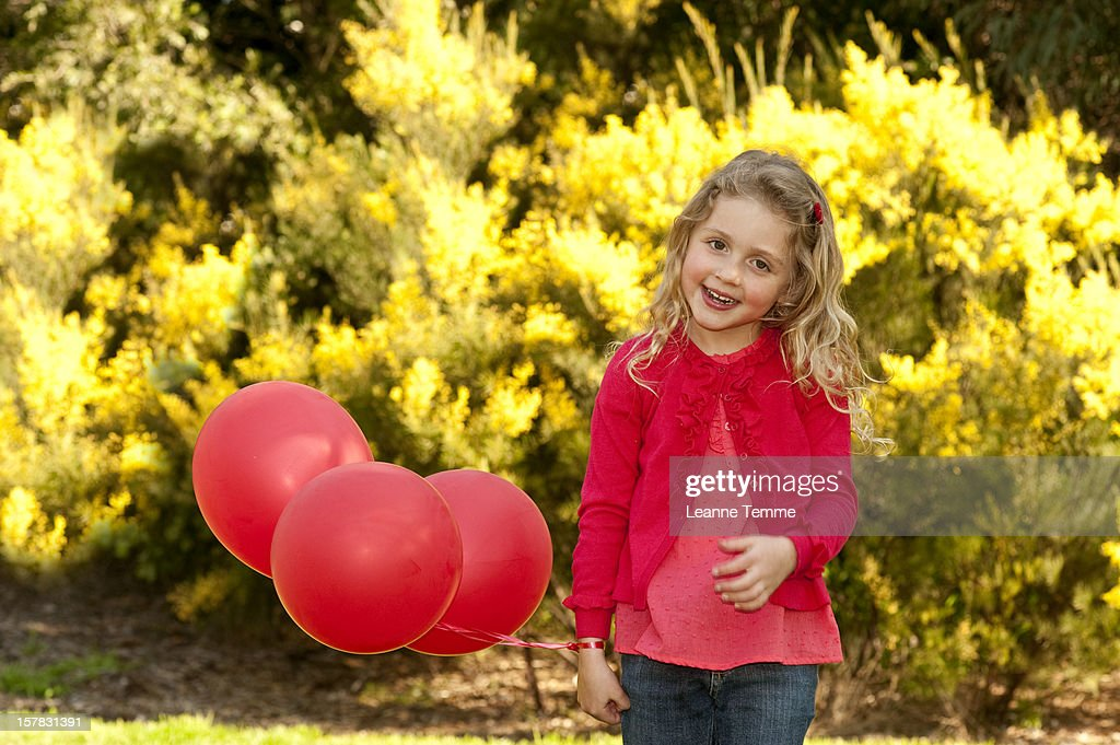 Six year old girl holding red balloons outside : Stock Photo