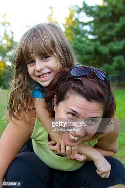 Six year old girl hugging her mother from behind