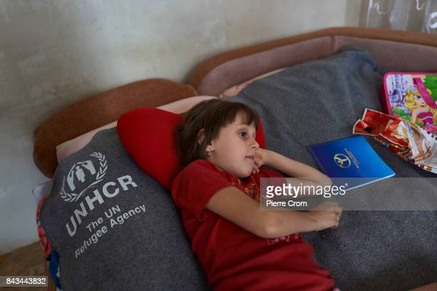 Six years old Natasha watches a cartoon laying on a United Nation blanket on September 06 2017 in Avdiivka Ukraine Natasha lives on the frontline and...