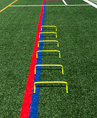 Six yellow mini banana hurdles are lined up in a staight line on a green turf field for speed and agility training.