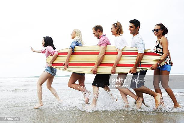 Six young adults carrying surfboard on beach