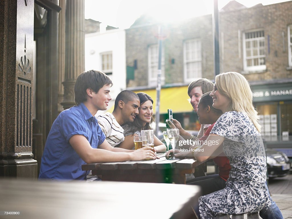 Six young adults sitting at outdoor pub table, man with mobile phone