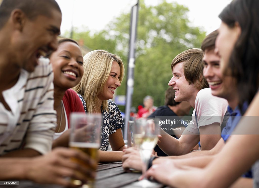 Six young adults sitting at outdoor pub table (differential focus) : Stock Photo