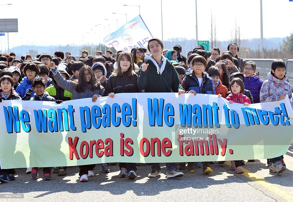 Sixteen-year-old Korean-American Jonathan Lee (C), an environmental and peace activist, and children march with a banner reading 'We want peace!' on the road linked to North Korea at a military che...