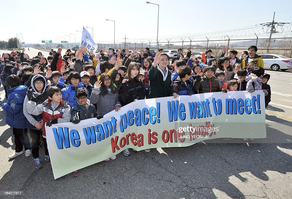 Sixteen-year-old Korean-American Jonathan Lee (C), an environmental and peace activist, and children march with a banner reading 'We want peace!' on the road linked to North Korea at a military check point in Paju near the Demilitarized Zone (DMZ) dividing the two Koreas on March 21, 2013 during his campaign for a peace forest on the tense inter-Korean border. Lee spearheaded this campaign and wanted the international community, along with North and South Korea, to agree to have children from both sides meet and create a Children's Peace Park in the DMZ. AFP PHOTO / JUNG YEON-JE