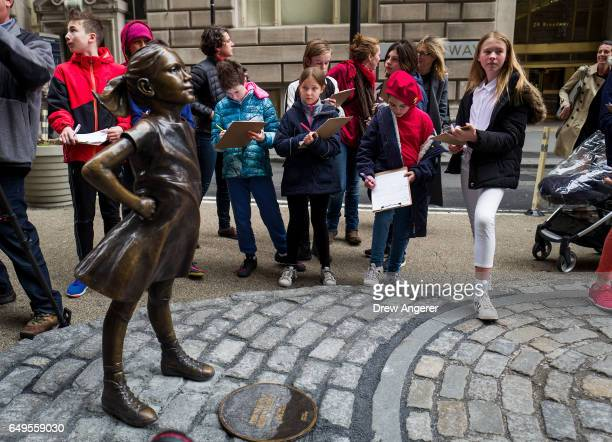 Sixth grade students from New York City's The Blue School take notes as they view 'The Fearless Girl' statue across from the iconic Wall Street...