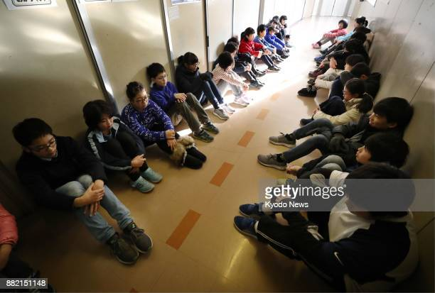 Sixth graders at an elementary school in Morioka in northeastern Japan's Iwate Prefecture sit in a corridor during an emergency drill on Nov 29 under...