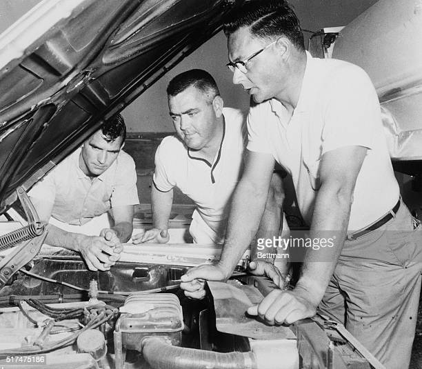Sixthranked NASCAR driver Junior Johnson of Ronda North Carolina and mechanics Horace Smith and Bob Auman make a final motor check on Johnson's 1965...