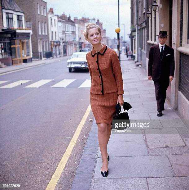 Sixties Fashion A young female model wearing a brown or copper coloured knitted skirt suit walks along a London street circa 1966