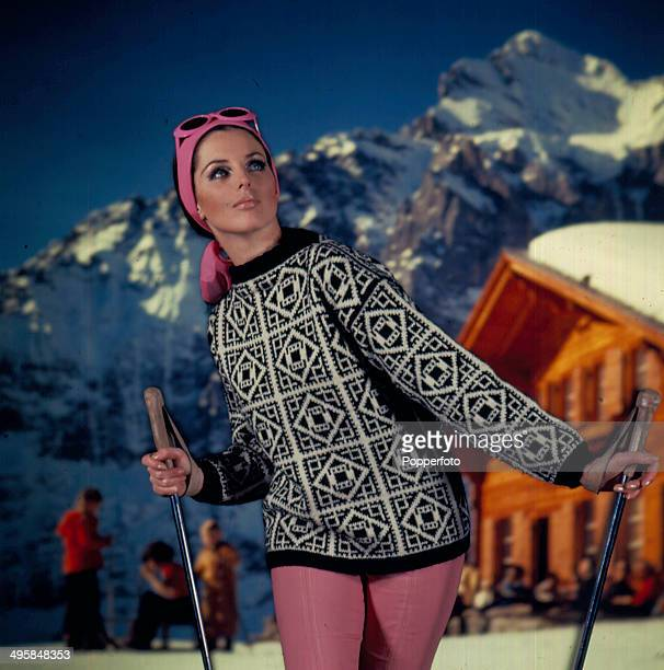 Sixties Fashion A young female model wears a black and white knitted jumper and pink leggings in front of a ski resort backdrop